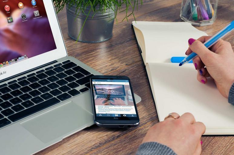 Jemand sitzt vor einem Computer, macht sich Notizen auf Papier, und ein Handy liegt daneben.